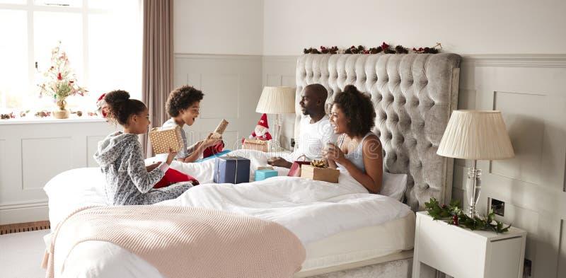 De jonge gemengde zitting van de rasfamilie op bed het openen giften in parentsï¿ slaapkamer ½ op Kerstmisochtend stock foto's