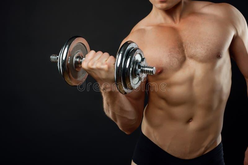 De jonge geschikte bodybuilder oefent met metaal uit stock afbeeldingen