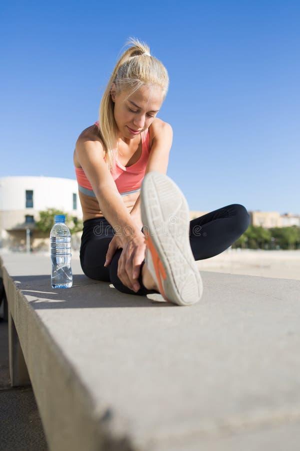 De jonge geschikte vrouw die opwarmingsoefeningen doen vóór begint met ochtend die in de verse lucht in werking wordt gesteld stock foto's