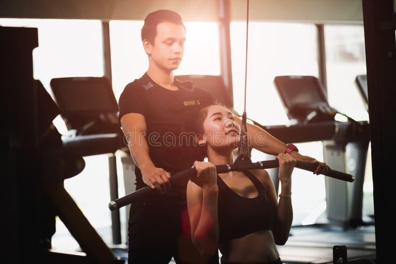 De jonge geschiktheids Aziatische vrouw voert met oefening-machine uit royalty-vrije stock foto's