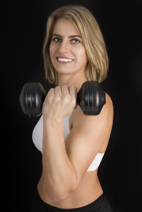 De jonge geschiktheidsvrouw hangt omhoog handengewichten. stock fotografie