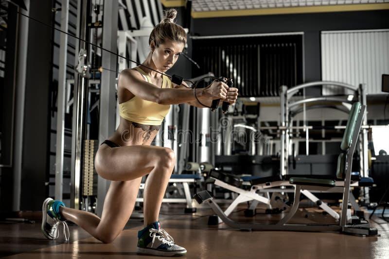 De jonge geschiktheidsvrouw voert oefening met oefening-machine Kabel uit stock foto's
