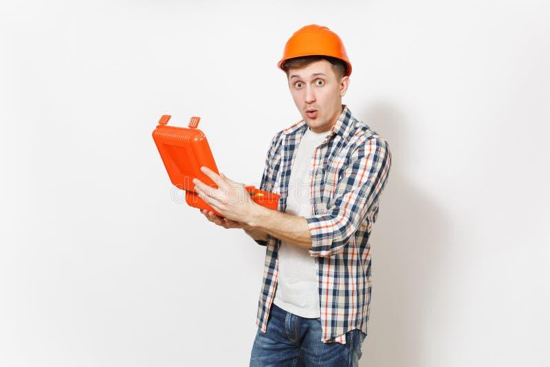 De jonge geschokte knappe mens in beschermende oranje bouwvakkerholding opende geval met geïsoleerde instrumenten of toolbox stock afbeeldingen