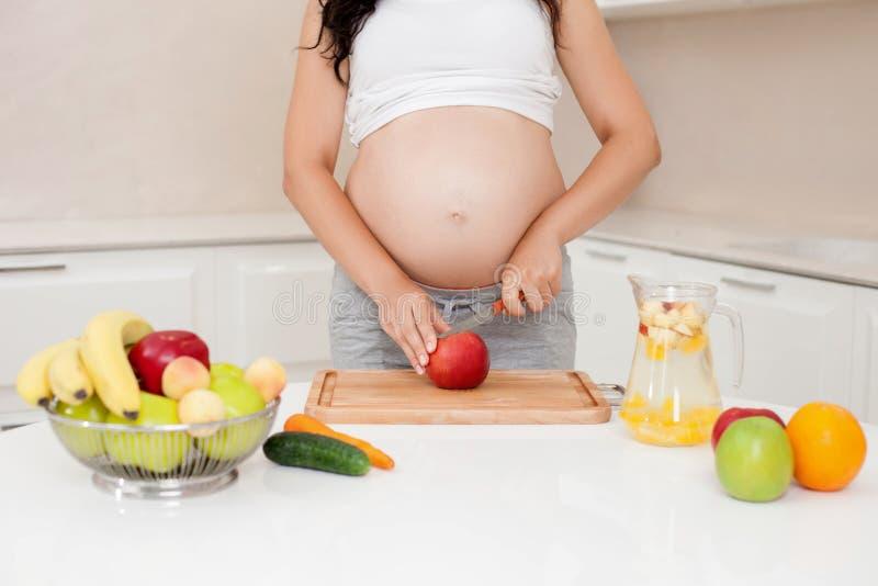 De jonge gezonde aanstaande moeder maakt sap stock afbeelding
