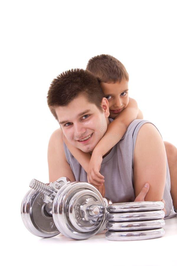 De jonge gezonde mens en de zoon oefenen bij gymnastiek uit stock afbeelding