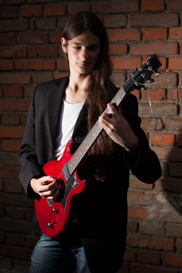 De jonge gitarist speelt zijn gitaar stock fotografie