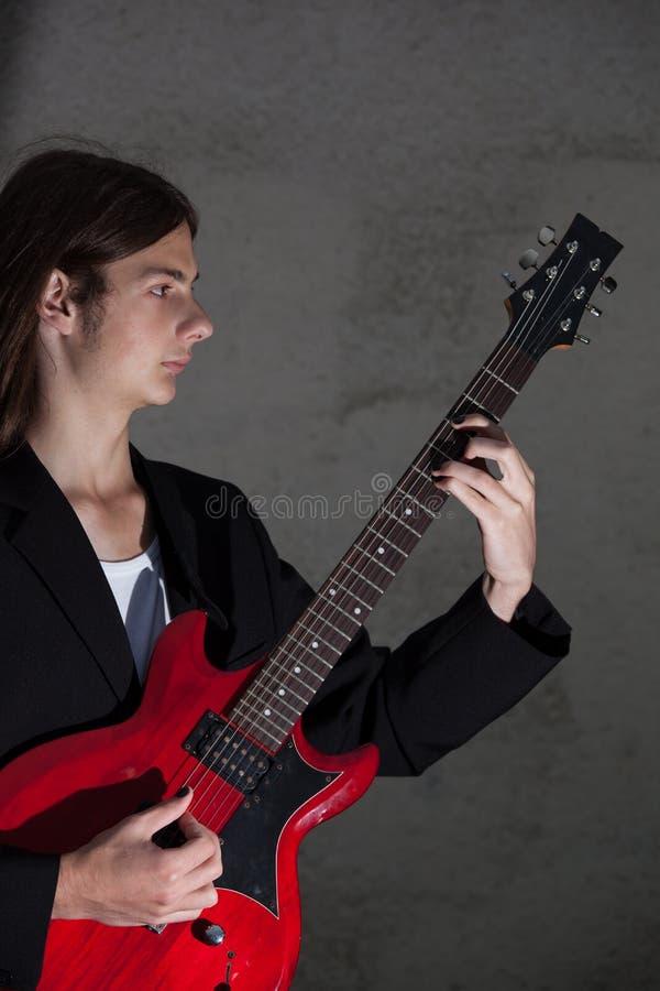 De jonge gitarist speelt zijn gitaar stock afbeelding