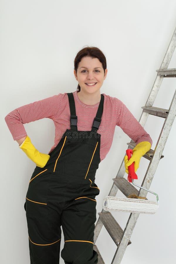 De jonge glimlachende arbeider schildert een ruimte stock foto's