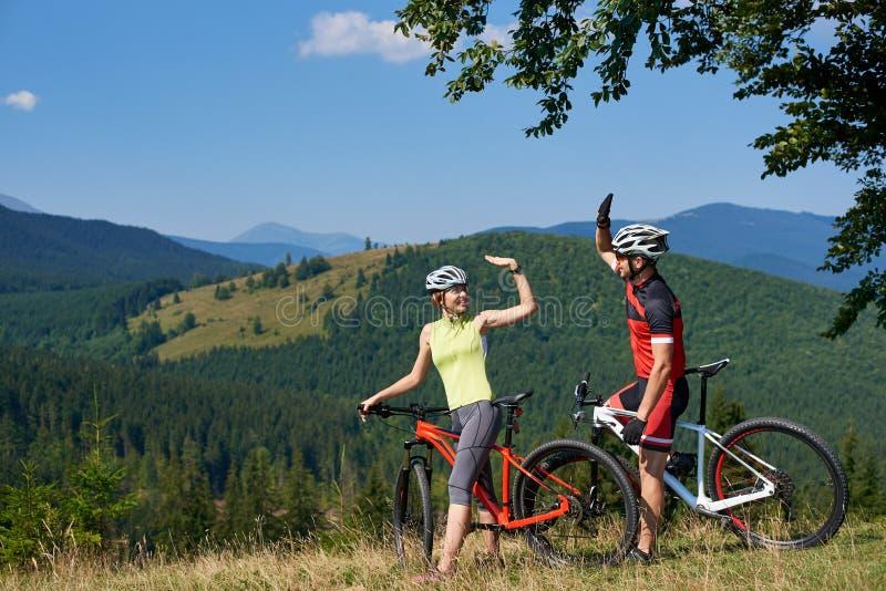 De jonge glimlachende fietsers koppelen, man en vrouw, die aan fietsen op grasrijke heuvel zich onder grote boom bevinden stock afbeelding