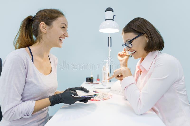 De jonge glimlachende manicure die van de schoonheidsspecialistvrouw aan een vrouwelijke cliënt spreken, doet manicure, vrouw die stock foto