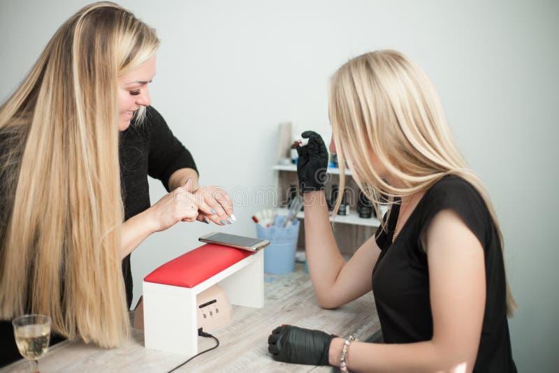 De jonge glimlachende manicure die van de schoonheidsspecialistvrouw aan een vrouwelijke cliënt spreken stock foto's