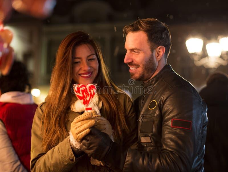 De jonge glimlachende mens in liefde geeft snoepjeshaard stock fotografie