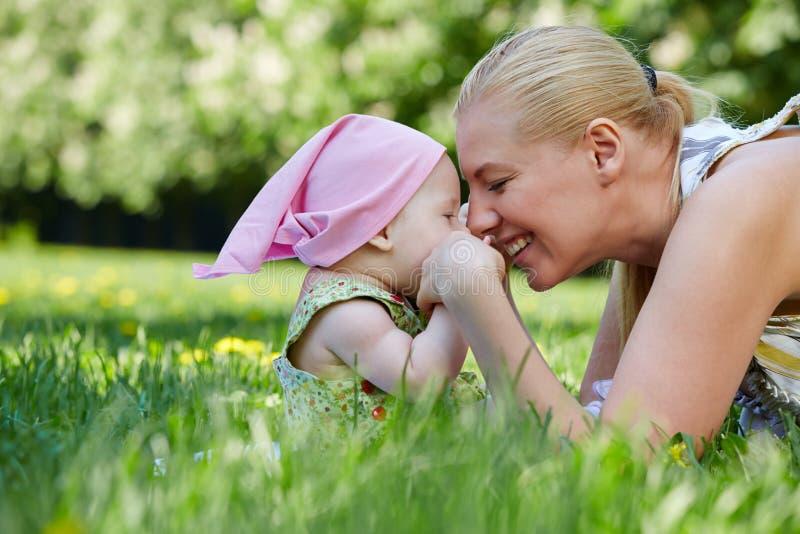 De jonge moeder en het baby-meisje wrijven neuzen, zittend op gras stock foto