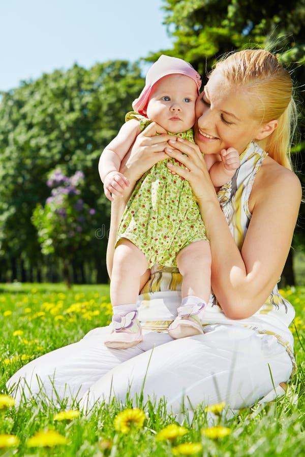 De jonge moeder zit in park en houdt baby royalty-vrije stock foto