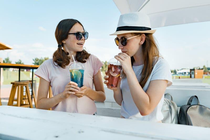 De jonge glimlachende tienermeisjes drinken koele verfrissende de zomerdranken op een hete zonnige dag in de zomer openluchtkoffi stock fotografie