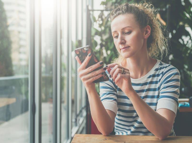 De jonge glimlachende vrouw in gestreepte blouse zit in koffie bij houten lijst dichtbij venster en gebruikt smartphone, lezend e royalty-vrije stock fotografie