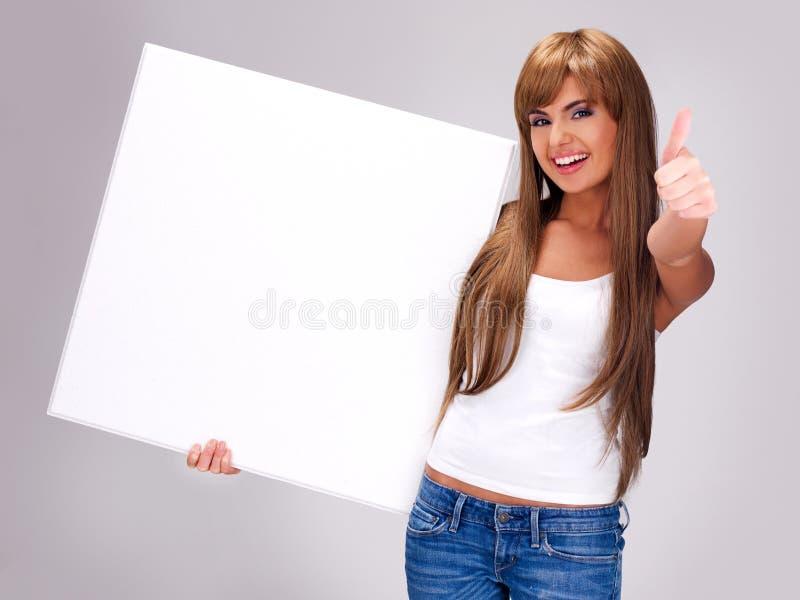 De jonge glimlachende vrouw houdt witte grote banner royalty-vrije stock foto
