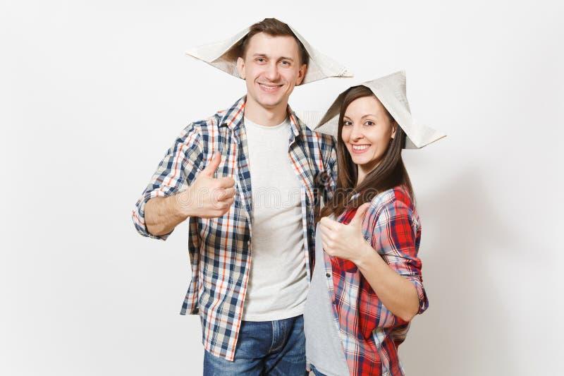 De jonge glimlachende vrouw, de man in vrijetijdskleding en krantenhoeden het tonen beduimelen omhoog Paar op witte achtergrond w royalty-vrije stock foto
