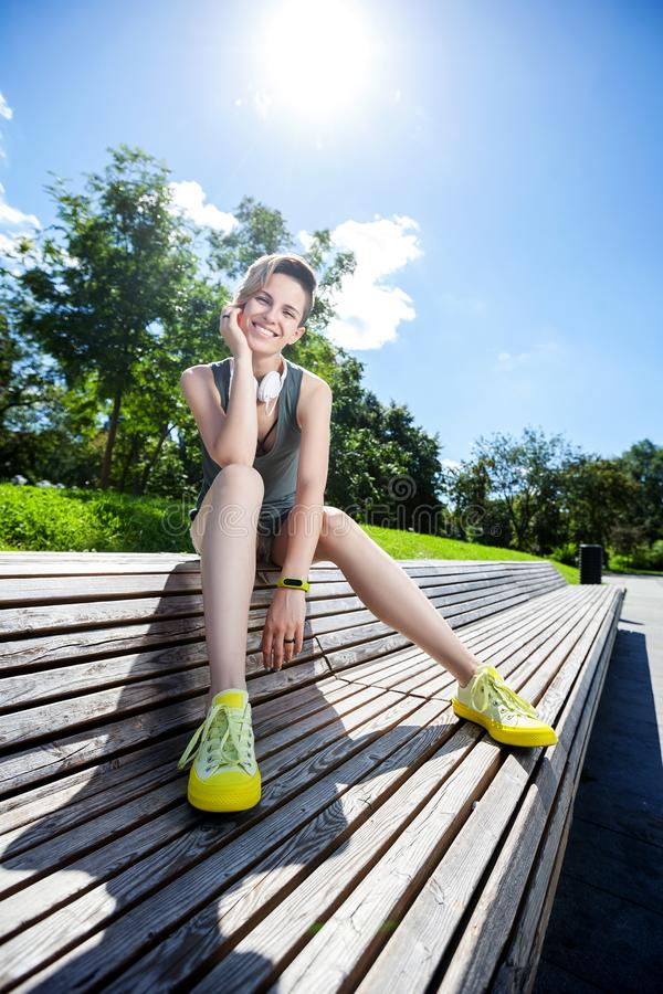 De jonge glimlachende vrouw rust op bank na jogging in park royalty-vrije stock foto