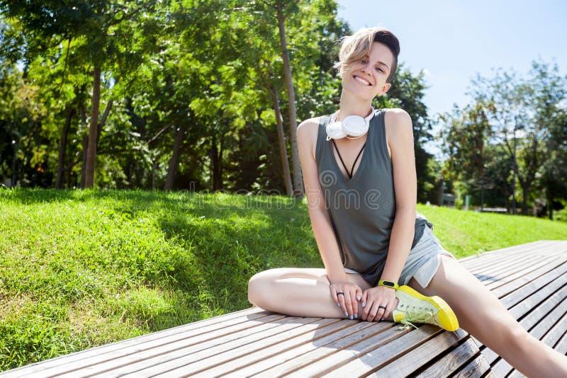 De jonge glimlachende vrouw rust op bank na jogging in park stock afbeelding