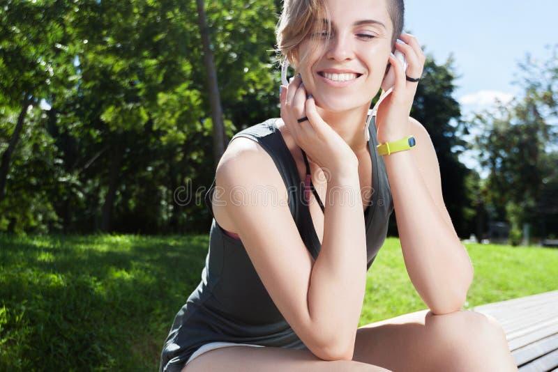 De jonge glimlachende vrouw rust op bank na jogging in park royalty-vrije stock afbeeldingen