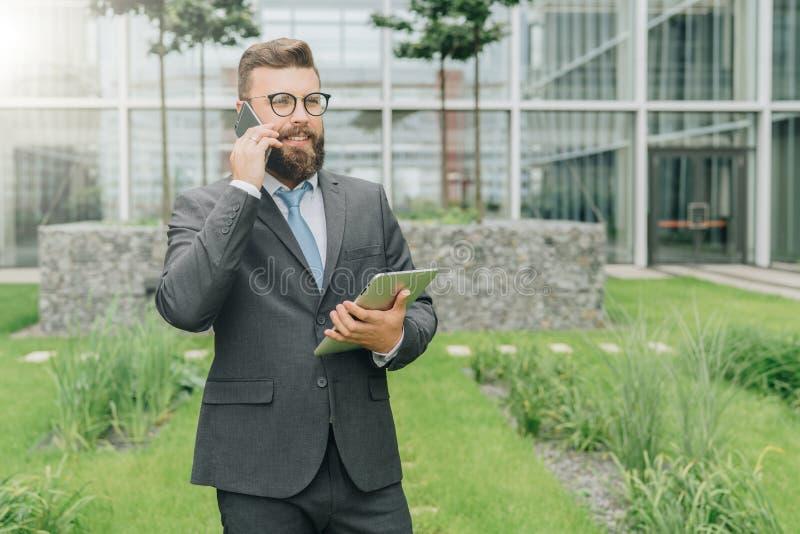 De jonge glimlachende zakenman in kostuum en band bevindt zich openlucht, houdt tabletcomputer en spreekt op zijn celtelefoon royalty-vrije stock foto