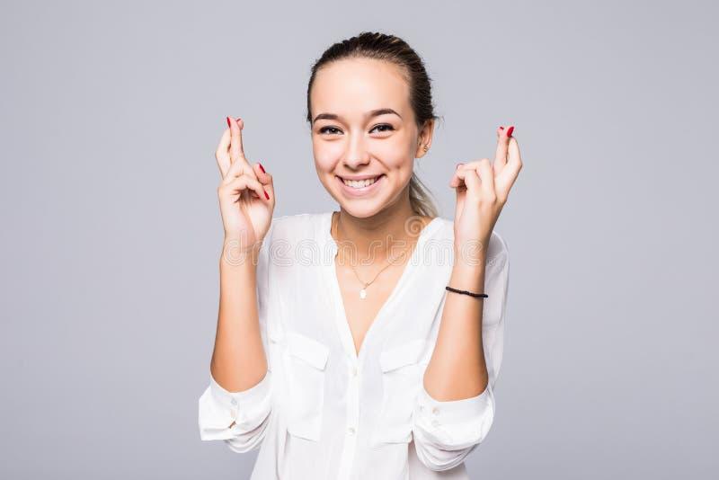 De jonge glimlachvrouw houdt vingers gekruist, hoopt voor goed die geluk, tegen grijze achtergrond met exemplaarruimte wordt geïs stock foto's