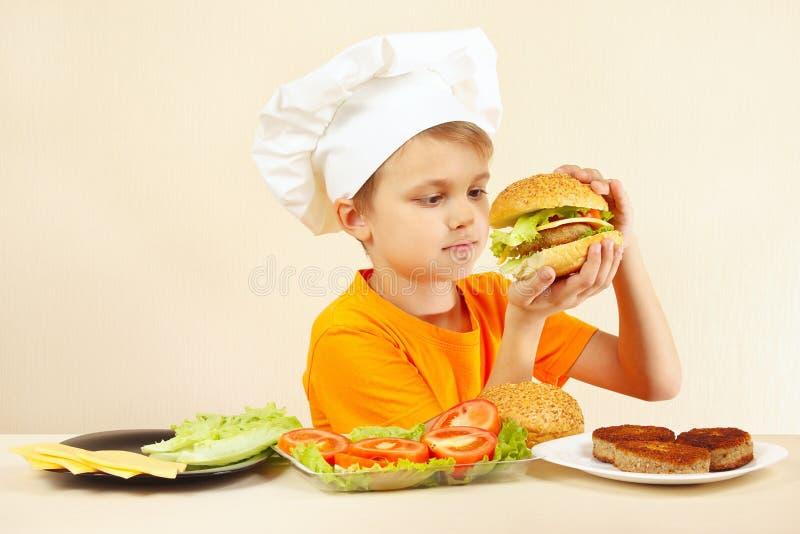De jonge grappige expressieve chef-kok geniet van gekookte hamburger royalty-vrije stock fotografie
