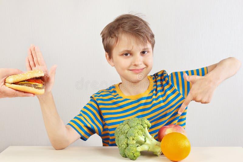 De jonge grappige jongen bij de lijst weigert hamburger ten gunste van fruit en groenten op witte achtergrond stock fotografie