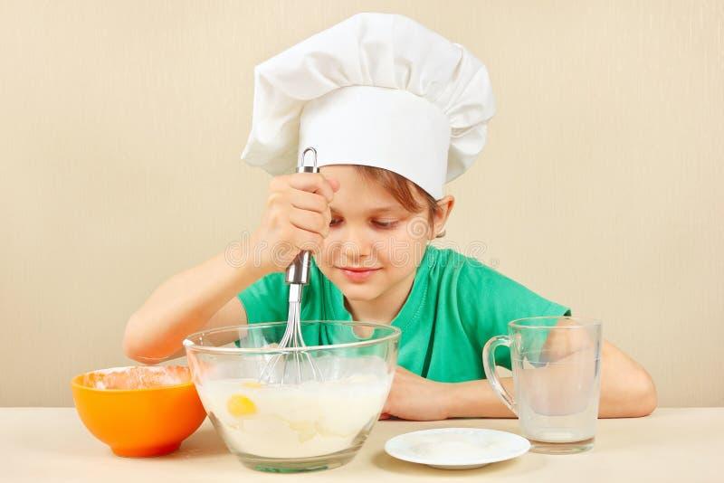 De jonge grappige jongen in chef-kokshoed bereidt het deeg voor bakselcake voor stock foto