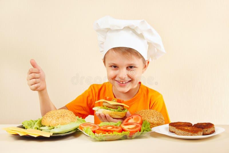 De jonge grappige jongen in chef-kokshoed toont hoe te om hamburger te koken royalty-vrije stock foto