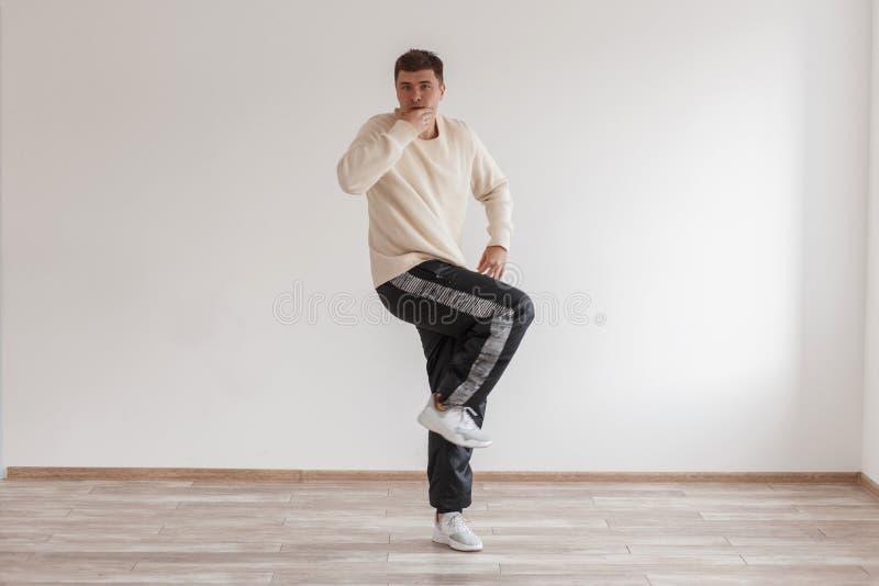 De jonge grappige kereldanser toont zijn vaardigheden die zich op zijn been bevinden stock afbeelding