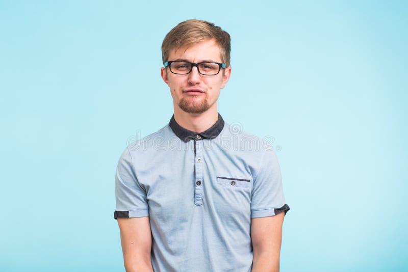 De jonge grappige mens draagt bril over blauwe achtergrond Gebaarde wonk kijkt ongelukkig royalty-vrije stock afbeelding