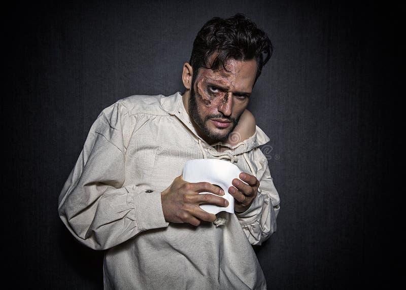 De jonge griezelige mens met gezicht bedekt met littekens en een wit masker, gekleed in een Spoor van de Opera ziet eruit royalty-vrije stock afbeeldingen