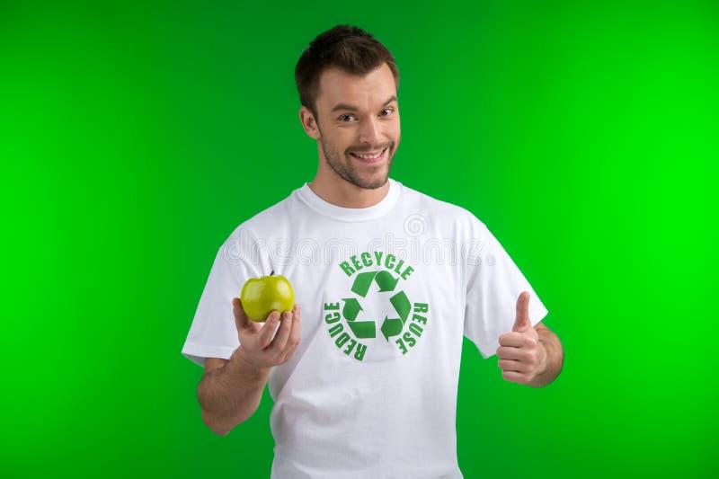 De jonge groene appel houden en mens die beduimelt omhoog doen stock foto