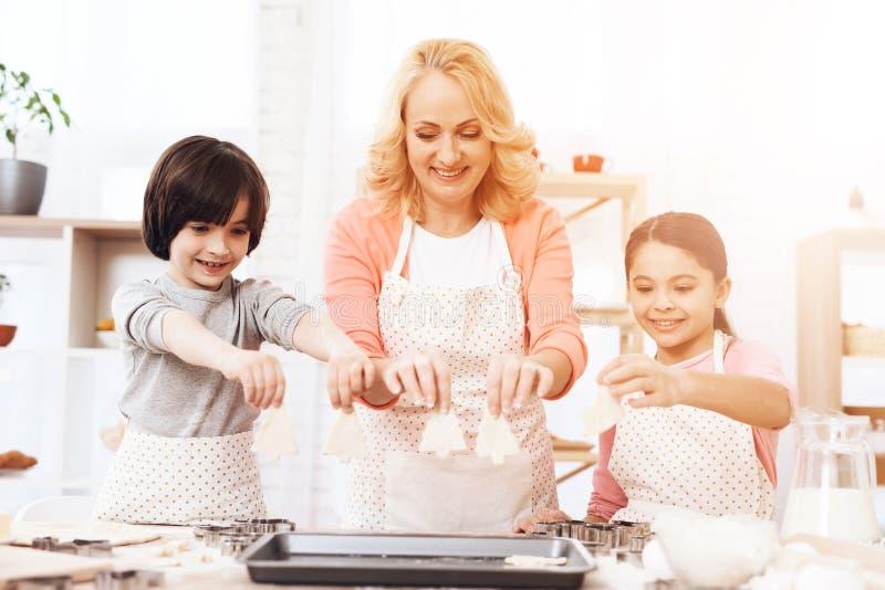 De jonge grootmoeder legt koekjesstukken voor deco in keuken Het mengsel van het chocoladekoekje, het bakken de vormen en het sno royalty-vrije stock fotografie