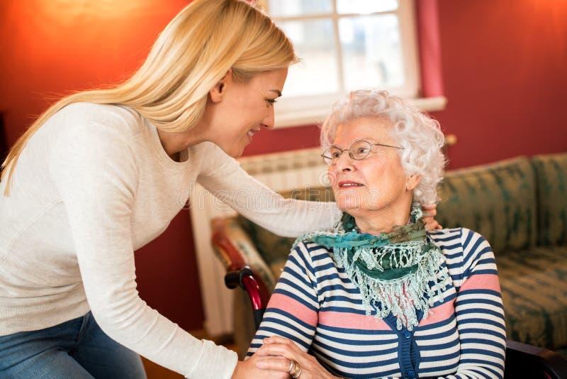 De jonge grootmoeder van het vrouwenbezoek en steunt haar over gezondheid royalty-vrije stock afbeeldingen
