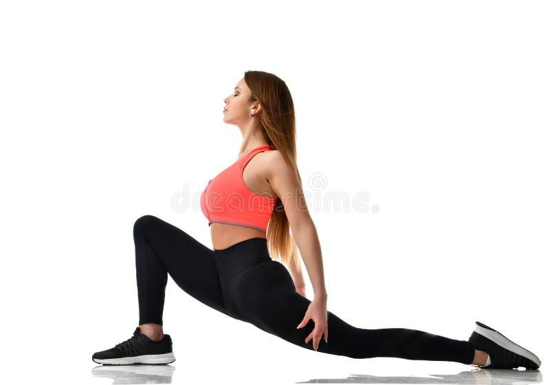 De jonge gymnastiek die van de sportvrouw uitrekkende die fitness oefeningstraining doen op een wit wordt geïsoleerd stock afbeelding