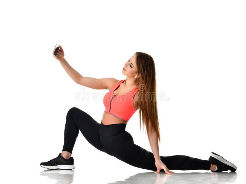 De jonge gymnastiek die van de sportvrouw uitrekkende die fitness oefeningstraining doen op een wit wordt geïsoleerd royalty-vrije stock afbeelding