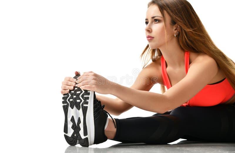 De jonge gymnastiek die van de sportvrouw uitrekkende die fitness oefeningstraining doen op een wit wordt geïsoleerd stock fotografie
