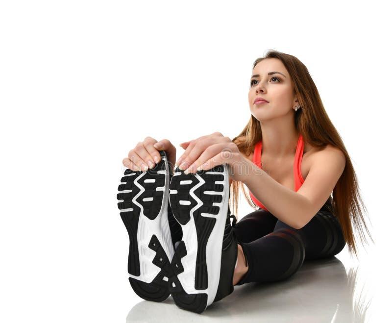 De jonge gymnastiek die van de sportvrouw uitrekkende fitness oefeningstraining op een wit doen stock foto