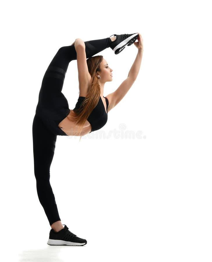 De jonge gymnastiek die van de sportvrouw uitrekkende gespleten die fitness oefeningstraining doen op een wit wordt geïsoleerd stock foto