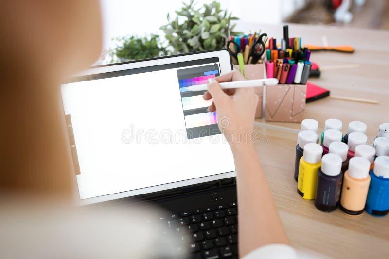 De jonge hand die van de ontwerpervrouw met haar digitale tablet op het kantoor werken royalty-vrije stock foto's