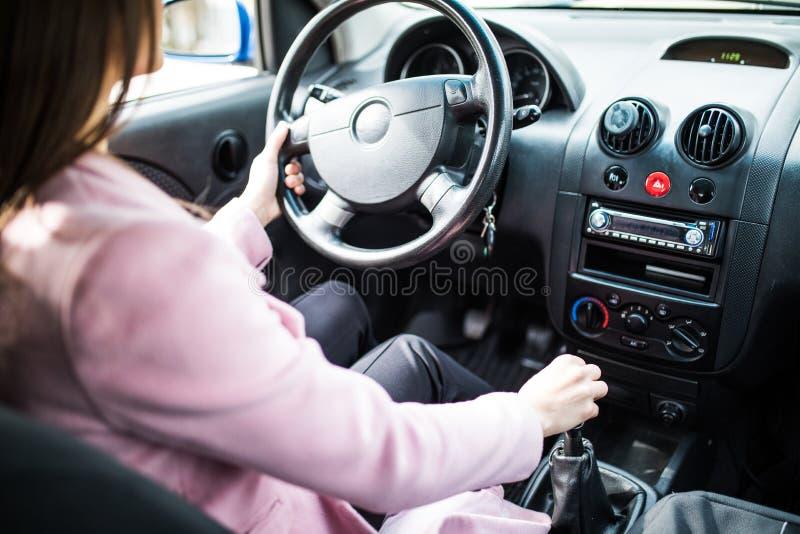 De jonge hand van de vrouwenholding op versnellingsbak in de auto stock afbeeldingen