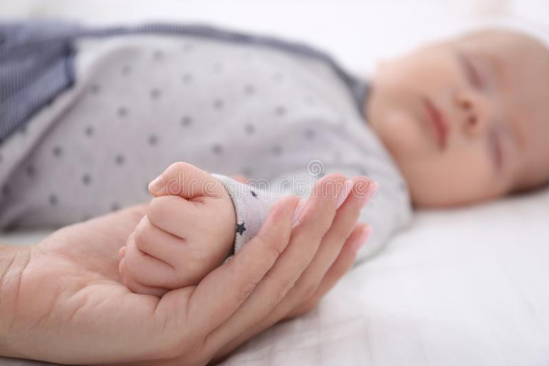 De jonge hand van de vrouwenholding van leuke slaapbaby, stock afbeeldingen