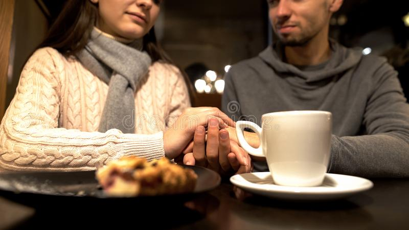 De jonge handen van de paarholding tijdens romantische datum in koffie, die van tijd samen genieten stock foto's