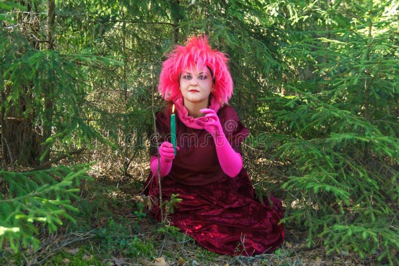 De jonge heks in purpere kleren met een kaars in van hem dient het bos in royalty-vrije stock foto's