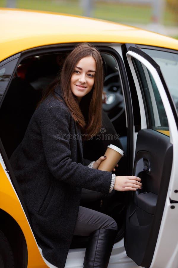 De jonge het glimlachen donkerbruine koffie van de vrouwenholding in taxi stock fotografie