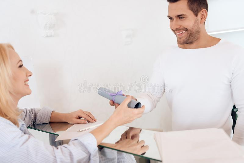 De jonge het glimlachen kerel overhandigt certificaat met lint aan rijpe blondevrouw royalty-vrije stock foto
