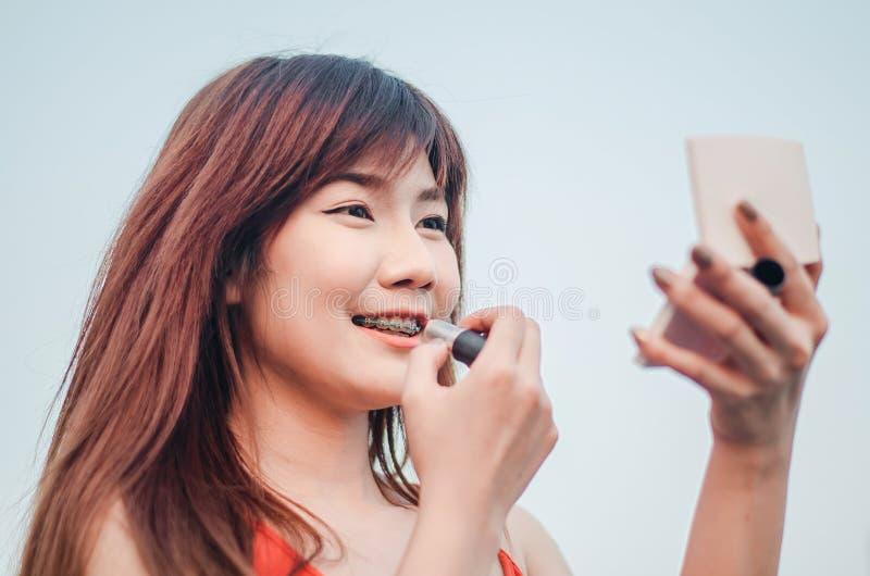De jonge het glimlachen lippen van de bedrijfsvrouwentekening met lippenstift die zich in openlucht over stad bevinden royalty-vrije stock fotografie